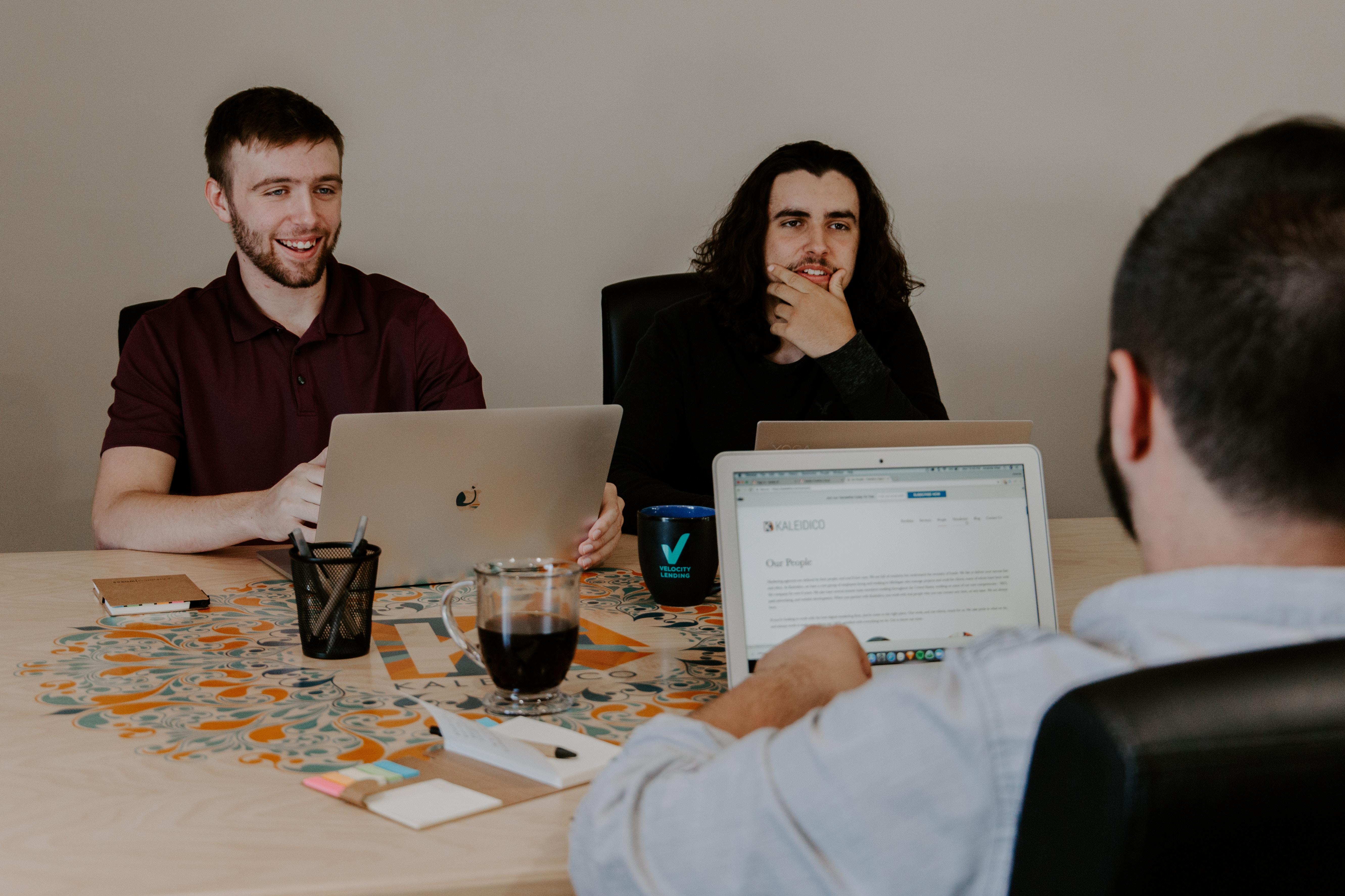 Traja muži sediaci pri stole s notebookmi