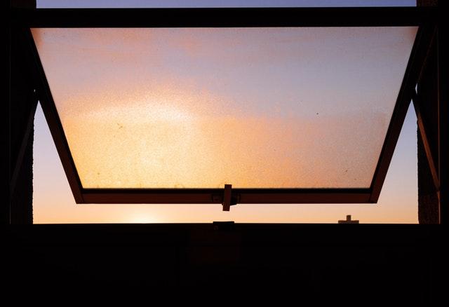 východ slnka cez okno