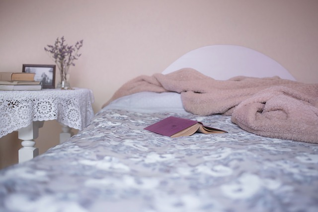Posteľ s kvetinovým prehozom, knihou a ružovou dekou.jpg