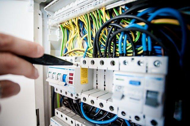 Človek používa skúšačku na elektrinu pri poistkách