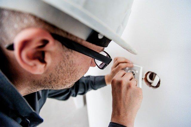Elektrikár v bielej prilbe a dioptrických okuliaroch montuje elektrickú zásuvku