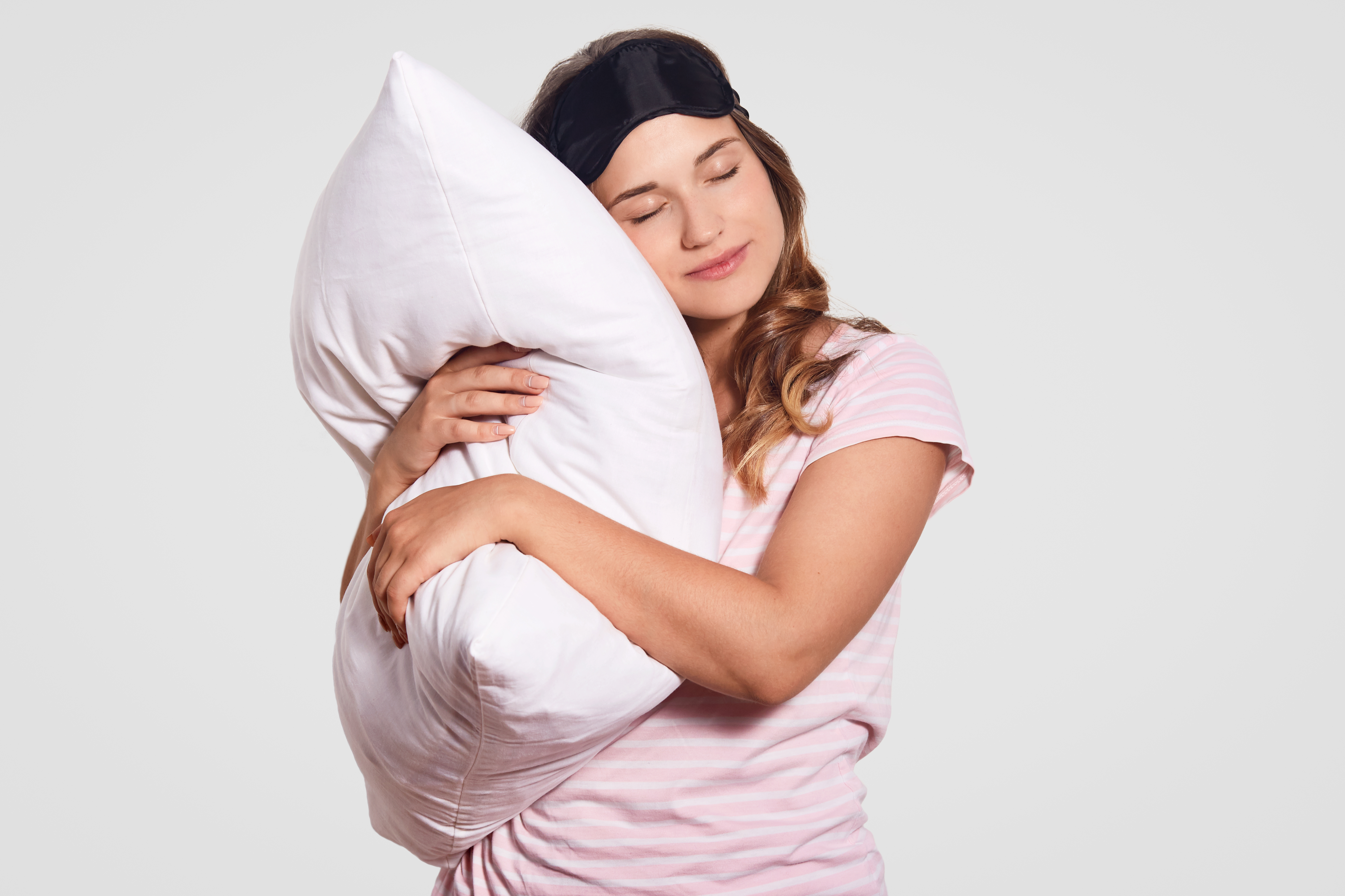 photo-of-european-woman-with-healthy-skin-leans-on-soft-pillow-wears-pyjamas-eyewear-on-head-poses-alone-on-white-has-sleepy-look-people-good-morning-concept