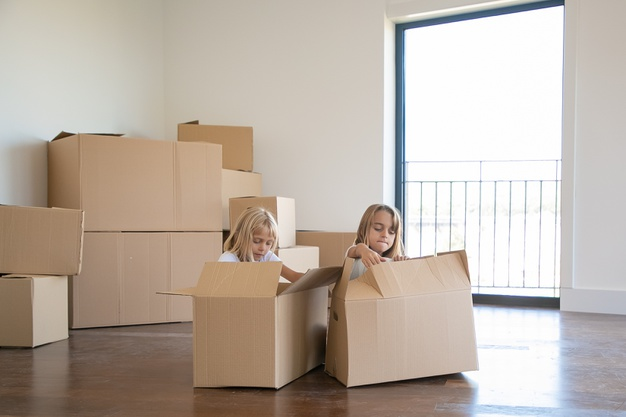 two-adorable-girls-unpacking-things-new-apartment-sitting-floor-near-open-cartoon-boxes_74855-10436